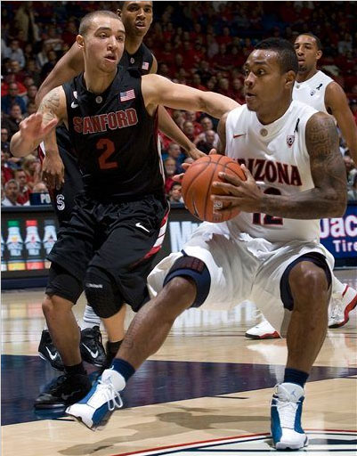Lamont Jones of Arizona wears the Flint Jordan Retro 13 while his teammate wears the white/Red colorway in the background.