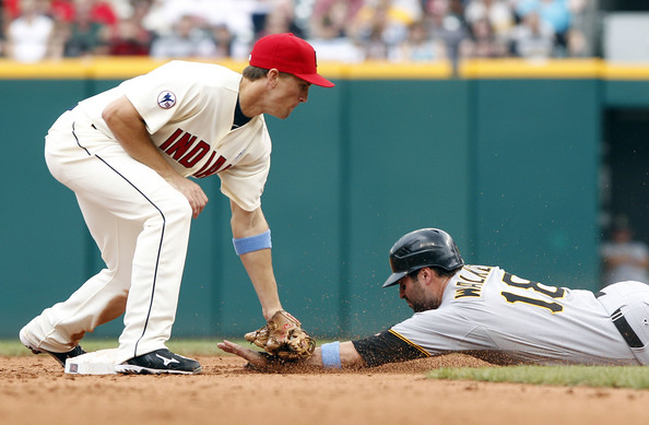 Cord Phelps applies the tag in his Mizuno 9-Spike cleats.