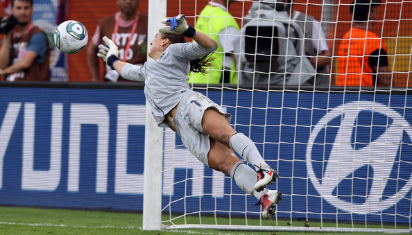 Hope Solo makes a diving save wearing Nike soccer cleats.