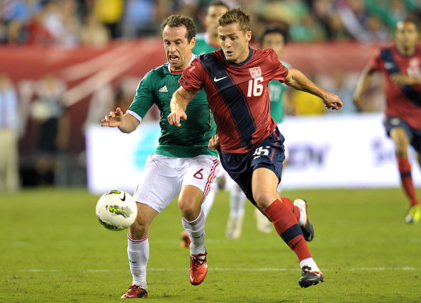 Robbie Rogers of the USA and Gerardo Torrado of Mexico battle for possession wearing Nike soccer cleats.