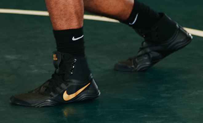 Image is focused on feet of wrestler as he stands on the mat wearing black and gold Nike Hypersweep wrestling shoes.