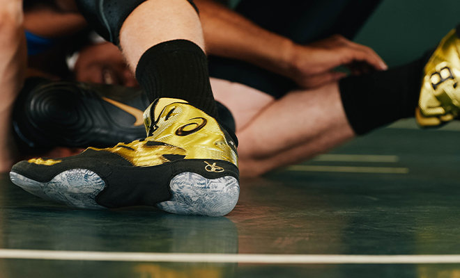 Image is focused on feet of wrestler as he's wrestles his opponent on the mat while wearing gold and black ASICS JB Elite IV wrestling shoes.