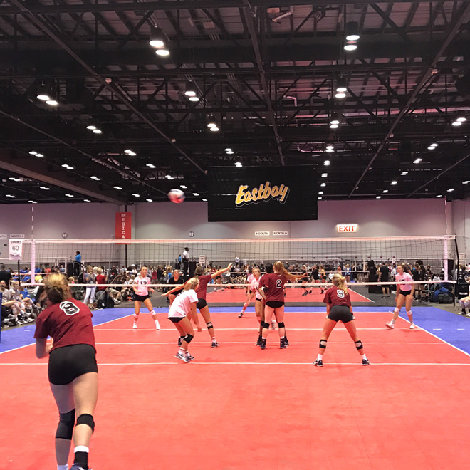 Two teams play on one of the many courts at the AAU Volleyball Championships