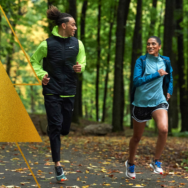 Man and woman running side by side on pavement covered in fallen leaves.