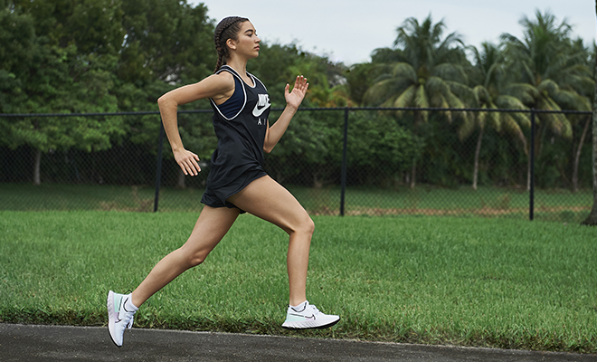 Female runner running on asphalt in Nike gear with lush green of trees and grass in the background.