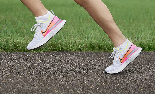 Closeup of female athlete's running shoes -- Nike React Infinity Run Flyknit (the sunrise collection).