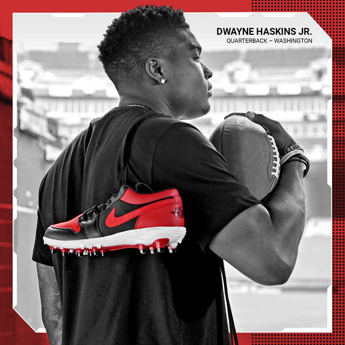 Dwayne Haskins Jr. looking at football field with cleats hung over shoulder