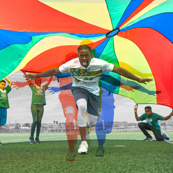 Davante Adams runs under colorful parachute on field.