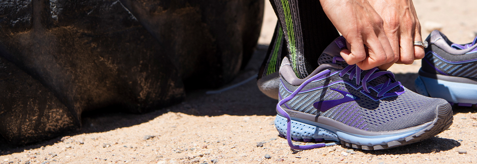 Athlete's hands tying laces of a pair of purple Brooks Ghost 12 shoes.