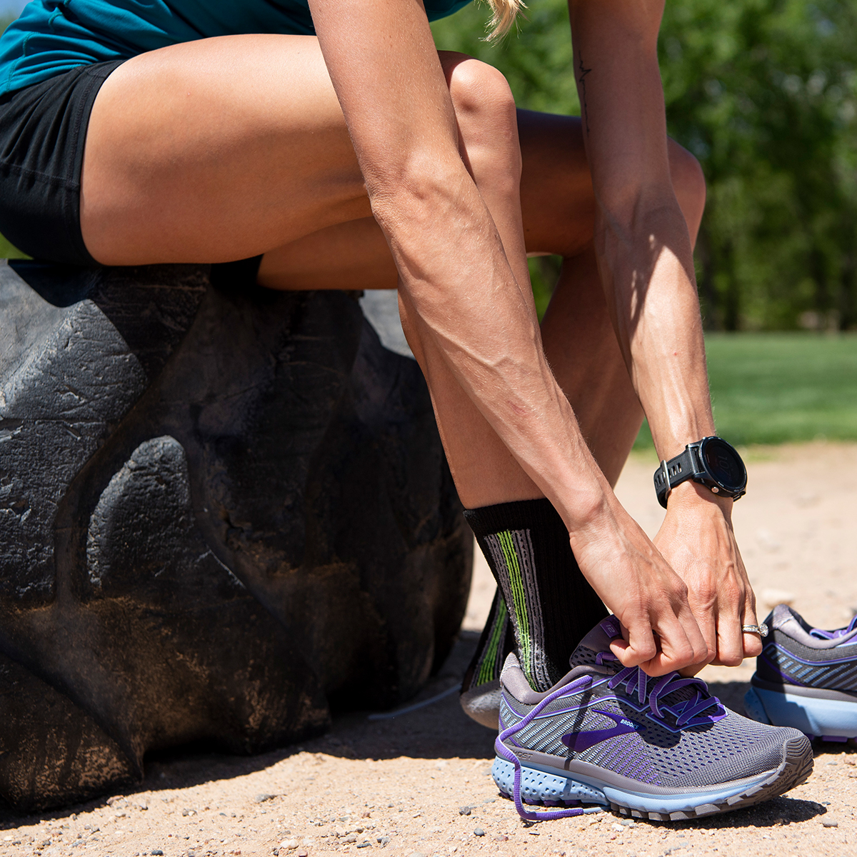 Brooks Beast runner tying the laces on a pair of purple Ghost 12s.