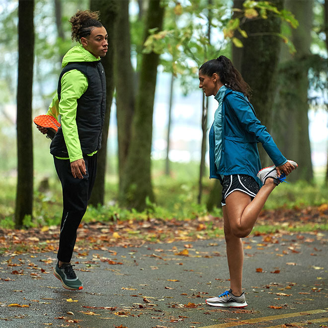 A man and woman, wearing Nike gear, stretch before their run on wet pavement with fallen leaves on the ground.
