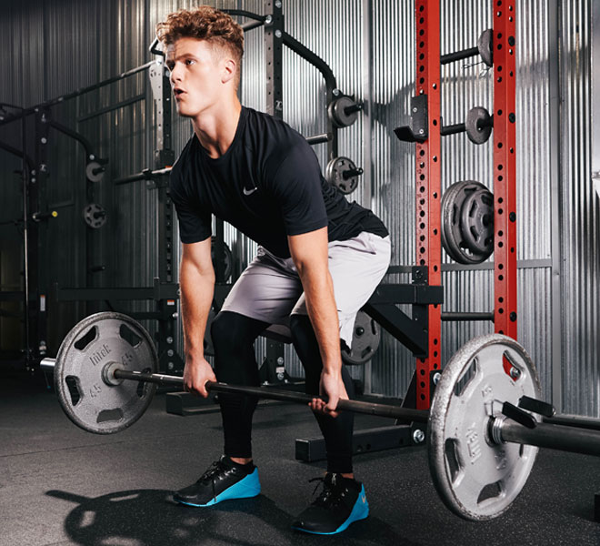 Male athlete lifting weights in the gym while wearing Nike Pro apparel and Nike Metcon shoes.