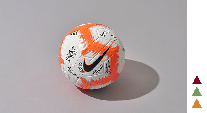 An orange and white Nike Strike Soccer Ball.
