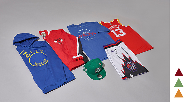 An assortment of fan gear laid out (a Golden State hoodie, a Chicago jacket, a Philadelphia T-shirt, a Houston jersey, Toronto shorts and a Boston hat).