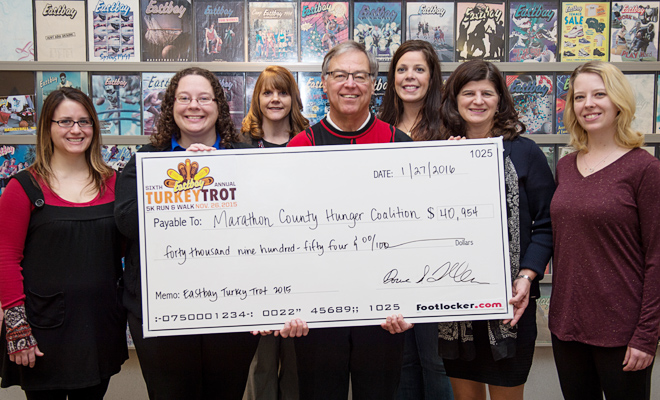 Group of Eastbay employees and Dave Eisenreich from the Hunger Coalition take photo with large donation check.