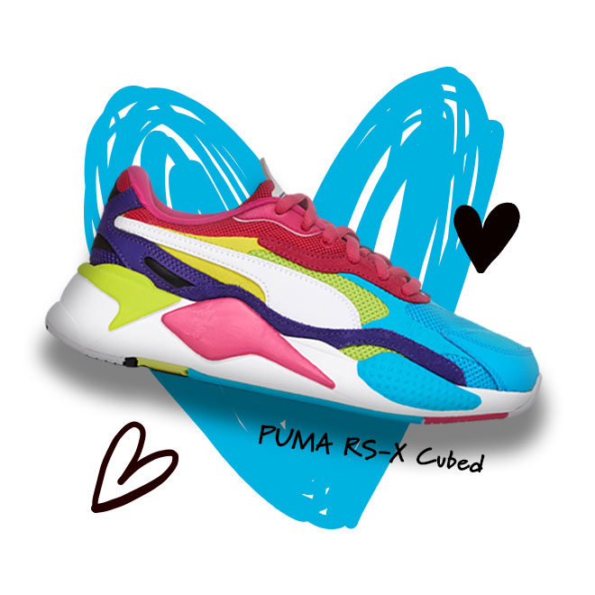 A PUMA RS-X Cubed sneaker in the Beetroot Purple/White/Purple colorway with a scribbled heart in the background.